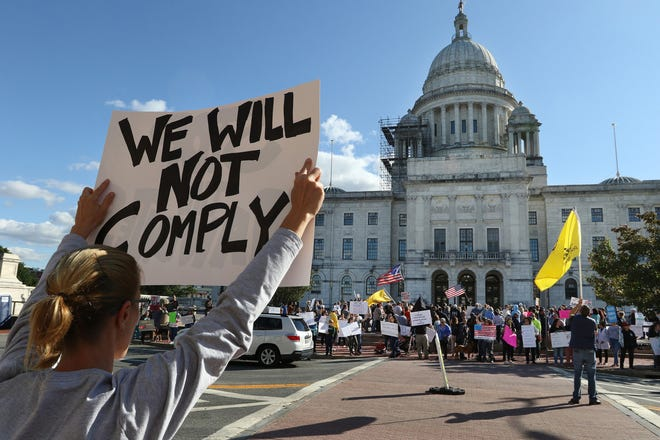 Hundreds gather at the State House on Friday to protest the state's health-care worker vaccination mandate.
