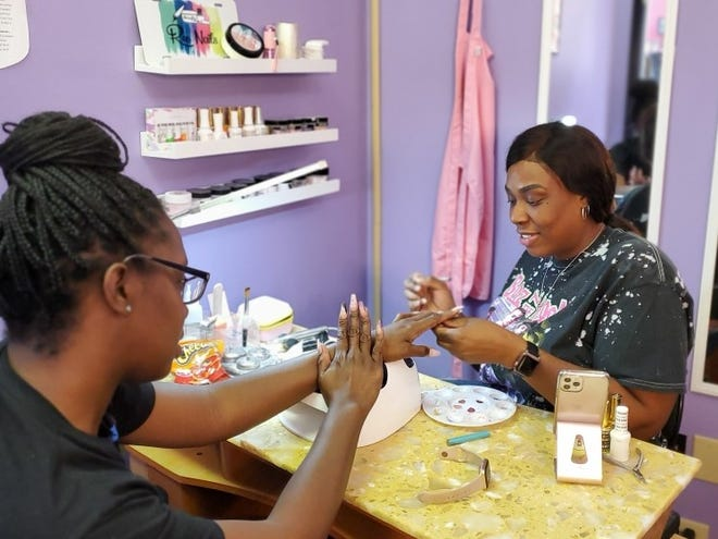 Client Shay Roland is pictured admiring the work of nail technician Shari Cooper.