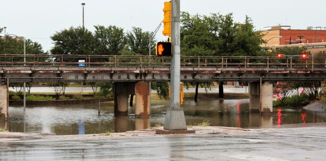 Red traffic lights and a pedestrian caution also warn motorists not to drive through the water-filled Butternut underpass Thursday evening. Abilene was deluged by more than 2 inches of rain, flooding streets and all underpasses.