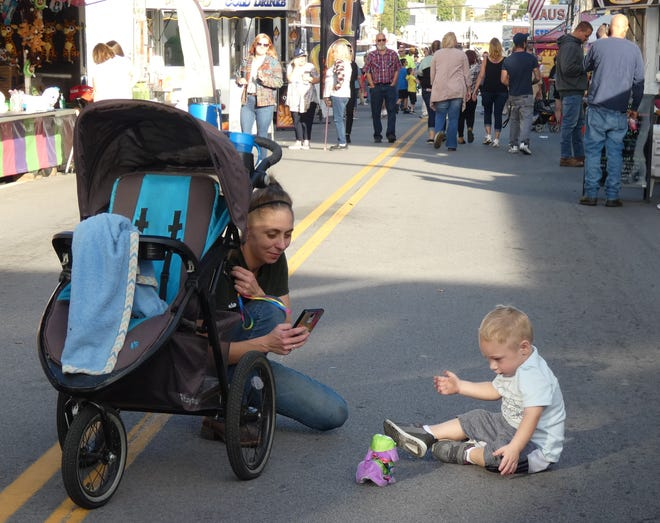 Mom Miranda Meeker of Galion watches as Brantley Agin, 2, plays with his toy dog on Thursday at the Galion Oktoberfest.