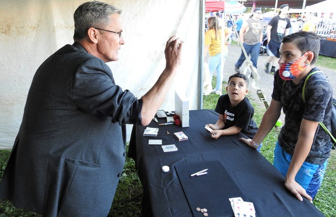 Dick McCune does a trick using bubbles for Miguel Arenas, 6, and Gabriel Ferrell, 14, at the Coshocton County Fair. McCune will be sharing his passion for magic and reptiles during a show at 2 p.m. Tuesday at the fair.