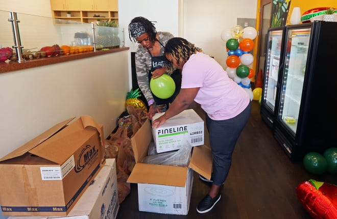 Imani Raiyne, left and Chandra Ellis, right, unpack supplies as they prepare for the opening Taste of Lindsay Heights Cafe that will open tomorrow at 1617 W. North Ave. in Milwaukee. The two entrepreneurs cafe feature food and drink made by local food entrepreneurs with such items as juices, ginger beer, pizza and cookies.