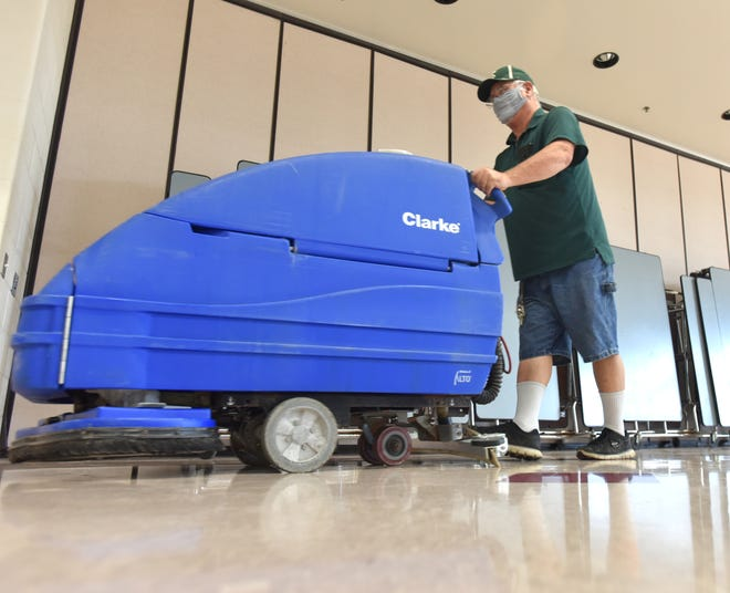 School custodian Kevin Flores touches up the cafeteria floor at an elementary school in Michigan on Oct. 1, 2021.