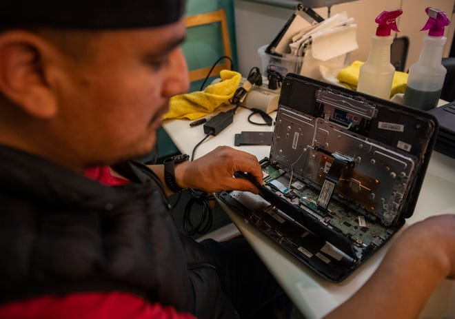 Jose Santiago, a volunteer at Loaves, Fishes & Computers helps repair a Chromebook in Salinas, Calif., on Thursday, Sept. 30, 2021.