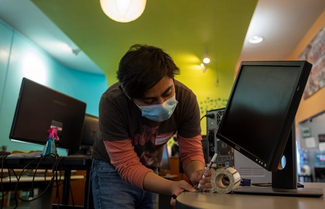 Gabriel Cano-Sandoval, a volunteer at Loaves, Fishes & Computers from California State University, Monterey Bay checks on different monitors to see if they're functioning properly in Salinas, Calif., on Thursday, Sept. 30, 2021.
