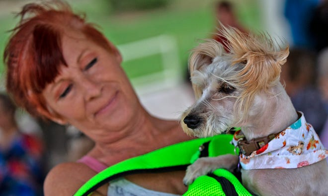 Jodi Sturgis and her dog Poppy wait for the start of the pet memorial service hosted by Concho Valley Paws near the International Waterlily Collection on Thursday, Sept. 30, 2021.