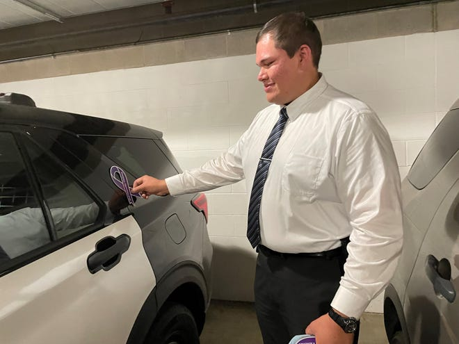 Detective Cole German, 29, puts a purple ribbon for Domestic Violence Awareness Month on a Sioux Falls Police Department car.