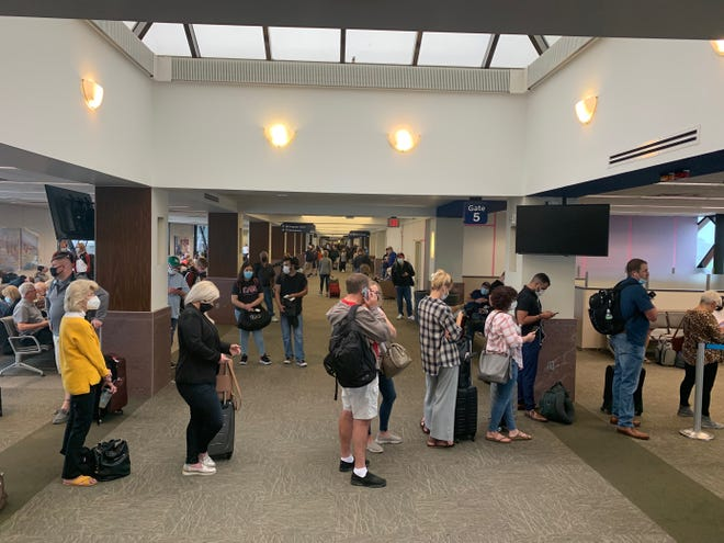 Passengers wait in line to rebook flights due to fog delays at the Sioux Falls Airport on Friday, Oct. 1.