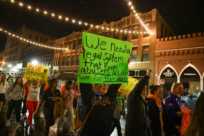 Marchers carry signs on St. Germain Street during the Take Back the Night march and rally Thursday, Sept. 30, 2021, in St. Cloud.