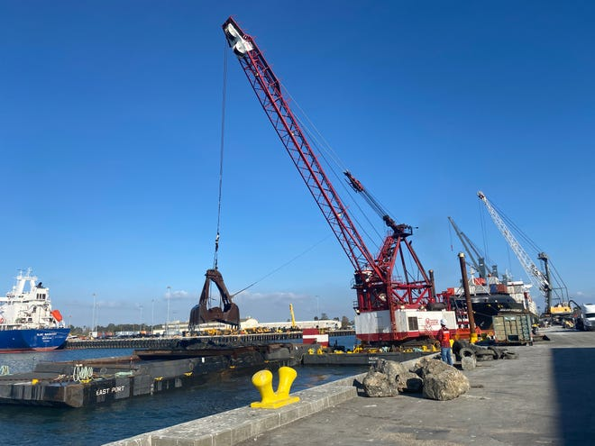 A conventional crane uses a clam bucket to dredge Port of Hueneme's south terminal in January 2020.