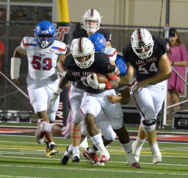 Lake Travis running back NIco Hamilton drags a Hays tackler for extra yardage in the first quarter of Friday's District 26-6A game. Hamilton rushed for two touchdowns in the Cavaliers' 69-21 win.