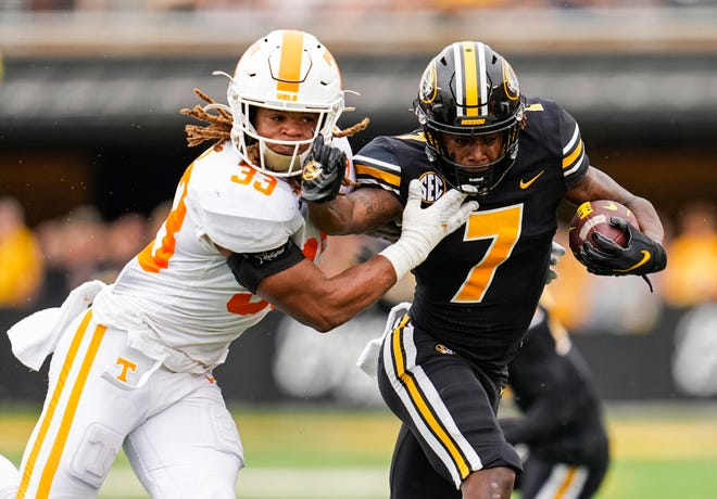 Missouri wide receiver Dominic Lovett (7) stiff-arms Tennessee linebacker Jeremy Banks (33) during the first half Saturday at Faurot Field.