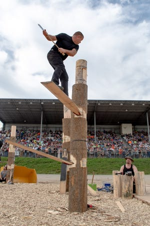Richard Jordan competes in the Springboard at the International Lumberjack Competition in front of a packed grandstand. Participants had to create two notches to place their Springboards to climb and then chop through the white pine log at the top.