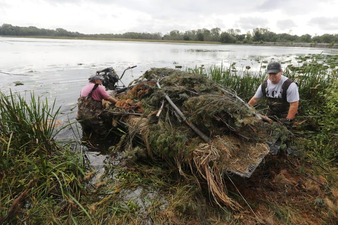 Tim Jones, President of the New Crystal Lake Club, left and board member Mike Bush, collect brush to add to one of the club's duck blinds, while the club was the site of the 2021 Outdoorsmen Heritage Festival and Fish Fry Saturday, Oct. 2, 2021, at the New Crystal Lake Club in Gulfport, Illinois. The club has a total of 15 blinds, including four pits. The two men were getting ready for the opening of duck season in the area, which is Oct. 30.