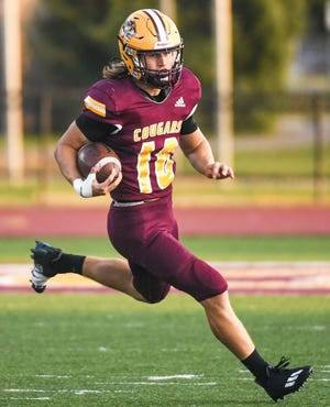 Bloomington North's Cody Mikulich (10) runs the ball during the game against Roncalli at North Friday evening.