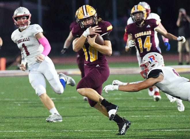 Bloomington North's Cody Mikulich (10) protects the ball as he runs during the game against Roncalli at North Friday evening.