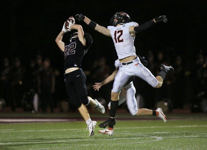 Buhler's Matthew Eddy (22) makes the catch past Augusta's Kaden McDaniel (12) then scores a touchdown during their game Friday night. Buhler defeated Augusta 56-21.