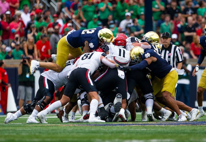 Notre Dame players try to stop a run during ND's 24-13 loss to Cincinnati on Saturday, Oct. 2, 2021, at Notre Dame Stadium.