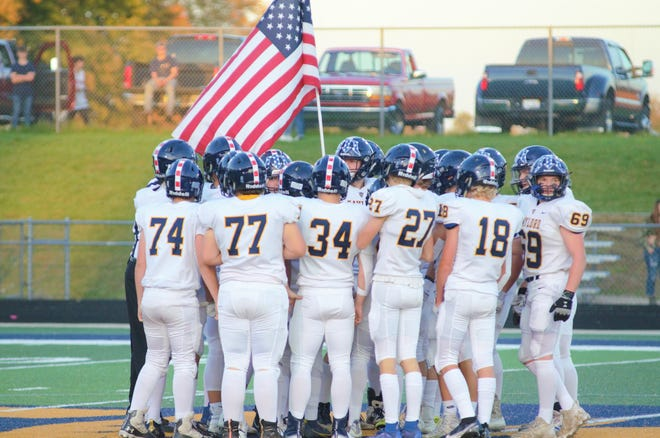 Gaylord football carries out an American flag before the game while donning their red, white, and blue helmets.