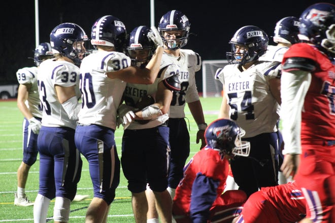 Exeter teammates congratulate Michael Dettore (29) after his touchdown run in the third quarter of Friday's win over Memorial.