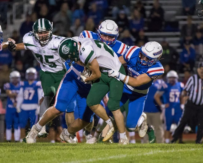 Winnacunnet's Jake Fredericks, left, and his older brother, Zach, tackle Dover's Brady McInnes during Friday's Division I football game in Hampton. Winnacunnet improved to 5-0 with the 40-6 win.