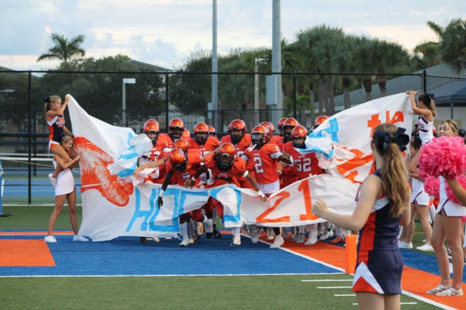 Benjamin players run through the banner ahead of a homecoming matchup with American Heritage on Oct. 1, 2021.