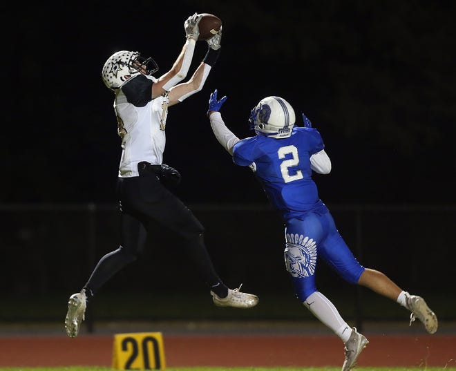 Davies' Matthew Patenaude, left, catches a long pass over Scituate defender Anthony Dupuis in the second quarter of Friday night's game, which was played in West Warwick.