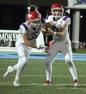 Martinsville junior Tyler Adkins hands off to senior Riddick Bolton during Friday's Mid-State Conference game at Perry Meridian.