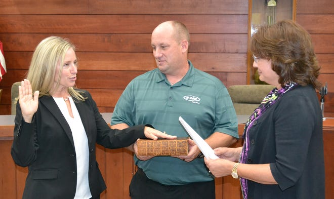Melissa Greene, left, takes the oath of office as her husband Kevin holds a family Bible. Greene was selected to serve on the Morgan County Council during a Republican caucus on Friday.