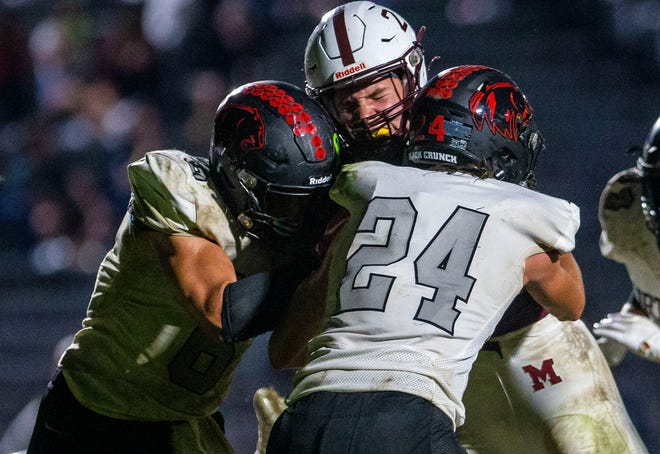 Mishawaka's Justin Fisher gets hit by NorthWood's Ethan Evers, left, and J.J. Payne at the goal line just before he scored during the Mishawaka vs. NorthWood football game Friday, Oct. 1, 2021 at Mishawaka High School.
