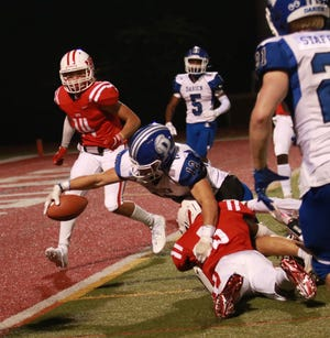 NFA's Gage Hinkley tries to stop Darien's John Wilson from going in for a touchdown during the Wildcats' 49-7 loss Friday night in Norwich.