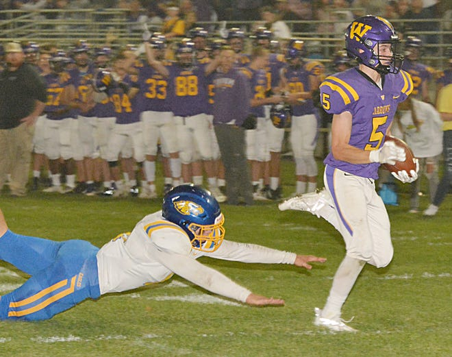 Watertown's Reese Stark (5) eludes a diving Aberdeen Central's Tayden Brownson to score on a 25-yard touchdown reception in the Arrows' 30-0 homecoming football victory Friday night at Watertown Stadium.