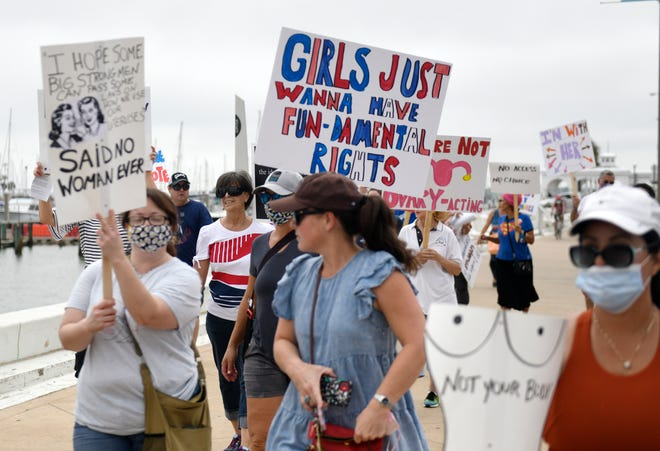 Protesters march along the Seawall ahead of the Supreme Court reconvening, Saturday, Oct. 2, 2021, as part of the Coastal Bend Women's Rights March. The Supreme Court will reconvene on Oct. 4.
