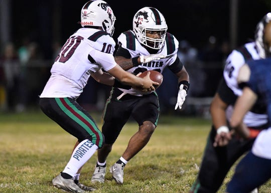 Cedar Creek QB JC Landicini (10) hands off to Ja'Quan Howard (22) during Friday nights football game against Holy Spirit. Cedar Creek defeated the top-ranked Spartans 7-6 in Absecon, N.J. Oct. 12, 2021.