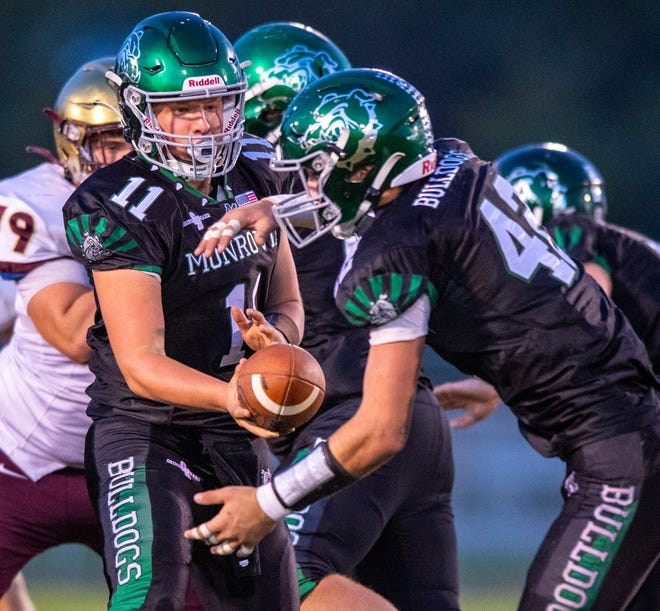 Monrovia High School junior Elias Wagner (11) hands the ball off to sophomore Brayton Belcher (42), in the backfield during the first half of an IHSAA varsity football game, Friday, Oct. 1, 2021, at Monrovia High School.