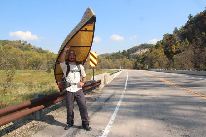 """Evan Hansen pauses on Thursday along Highway 74 near Whitewater State Park in southeastern Minnesota on his """"Portage For A Purpose."""" Hansen is carrying a canoe across Minnesota to raise awareness and funds for suicide prevention. He plans to finish his walk at the Mississippi River in Fountain City, Wis."""