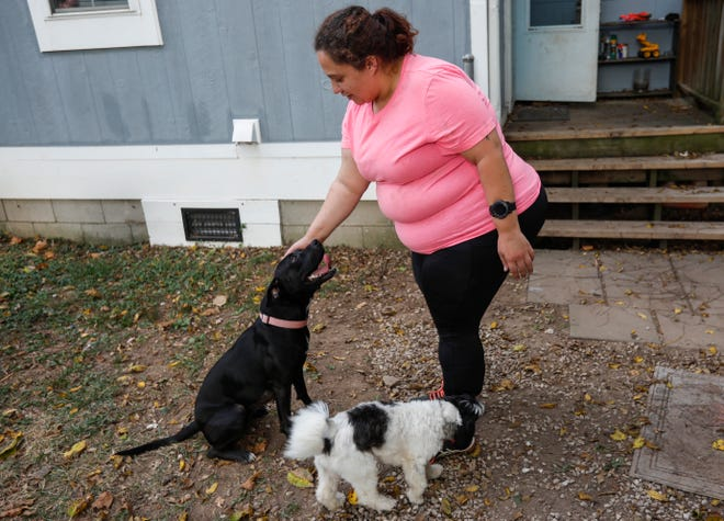 Alanna Livingston pets her foster dog Panther as her dog Lelu walks by on Thursday, Sep. 30, 2021.