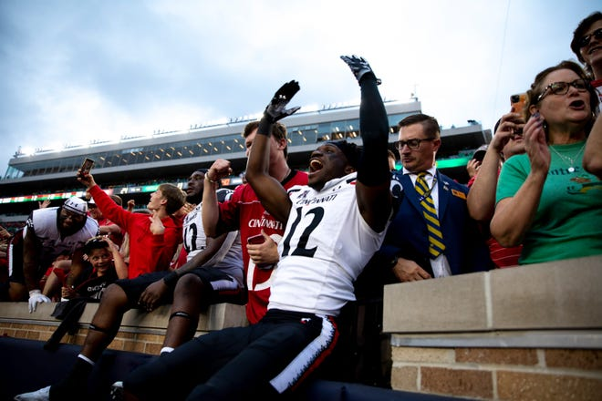 Bearcats cornerback Todd Bumphis celebrates with fans after they defeated the Fighting Irish 24-13.