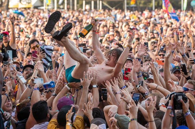 Marc Rebillet crowd surfs with a bottle of champagne during his performance at the Austin City Limits Music Festival in Zilker Park on Sunday October 3, 2021.