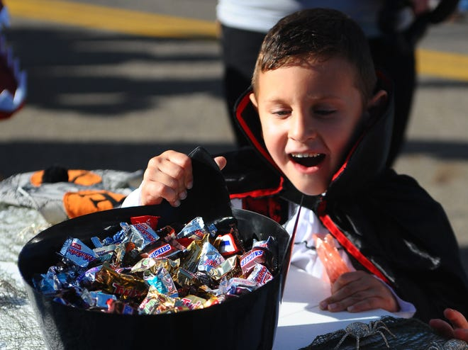 Isaac Wilson, 5, dressed as a vampire, excitedly smiles as he chooses a treat during the Duck Duck Downtown Jeep Crawl and Ghost Walk on Saturday, Oct. 2, 2021, in downtown Alliance.