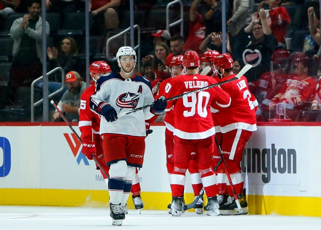 Columbus Blue Jackets defenseman Scott Harrington, left, skates away as Detroit Red Wings center Dylan Larkin is surrounded by teammates, including center Joe Veleno (90) and defenseman Nick Leddy, right, while celebrating Larkin's goal during the second period of an NHL hockey game Saturday, Oct. 2, 2021, in Detroit.