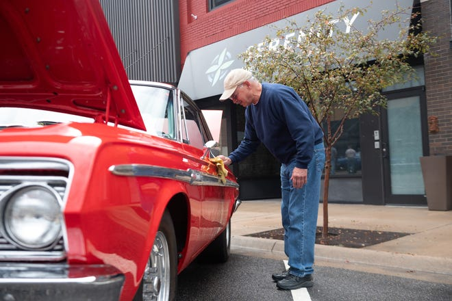Larry Zahn from Salina wipes down his 1963 Red Sport Fury after a rainy Saturday morning in preparation for the Rod Run judging on Main Street in Hutchinson and the first Hutchinson Fall Festival.