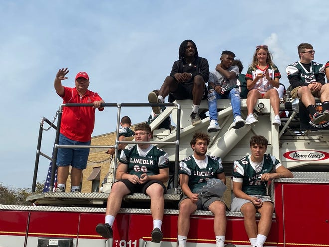 The Lincoln tradition continues as the Railer Football players ride atop a fire truck. Railer flag bearer Tim McDougall waves to the fans watching Friday's Homecoming parade in downtown Lincoln. The Railer Football team won their game against Mattoon beating the Green Wave 35-34.