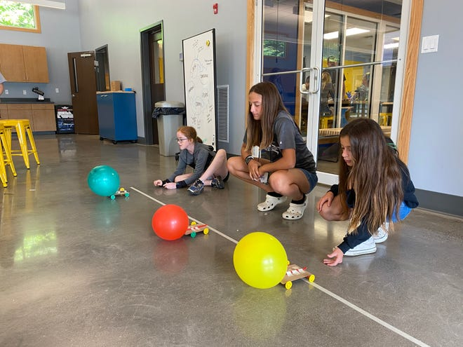 Mineral County 4-H members Megan Weaver, Abby DelSignore and Libby DelSignore test balloon cars to learn the science and engineering design concepts in the WVU Annette Boggs Educational Center.