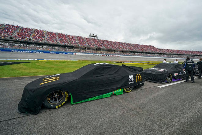 NASCAR Cup Series cars sit covered on pit road before attempting to start the race Sunday in Talladega, Ala. Officials postponed the playoff race until Monday due to rain.