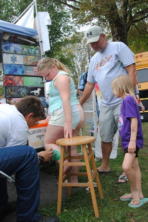 The Airbrush Tattoos artist Ryan Shumaker paints a flower on Miranda McCorkle's leg under the watchful eyes of her dad, Dave, and sister Aubrey, all of Somerset, Sunday afternoon at the annual Confluence PumpkinFest celebration.