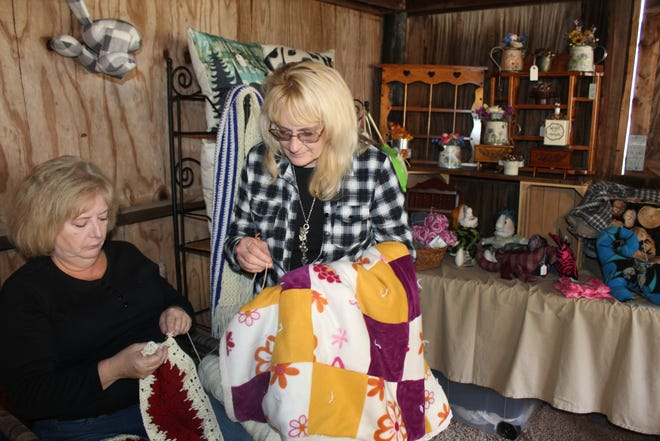 Christine Blubaugh (seated) and Tracey Koontz of Berlin display some of their homemade creations during this year's Springs Folk Festival this past weekend as part of their business Windows Through Time.