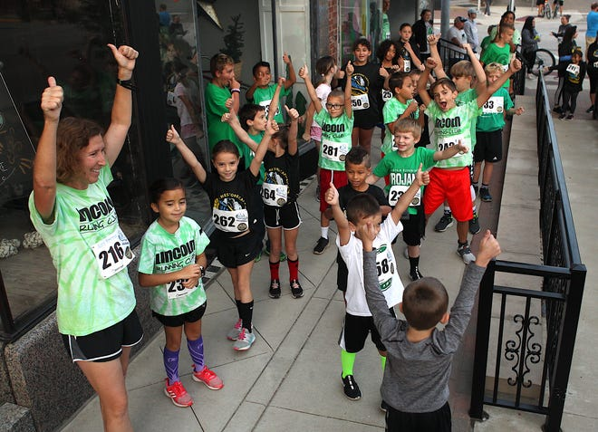 Amy Spence, left, leads the Lincoln Elementary Running Club in a motivational thumbs up after doing warm up exercises before the start of the races.