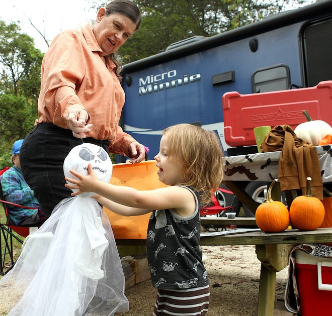 Ari Decker helps her Grandmother Maggie Miller with Halloween decorations Saturday afternoon at the Spring Mill Campground. The campgound was full, with every site decorated with imaginative Halloween/fall themes.