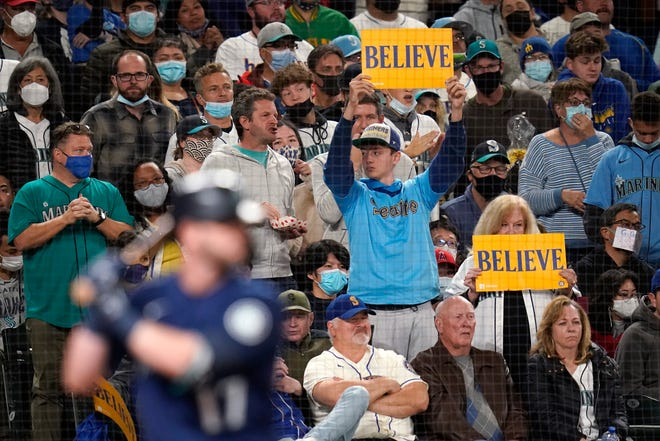 """Seattle Mariners' fans hold up signs reading """"Believe"""" as Mariners' Mitch Haniger comes to bat in the sixth inning of a baseball game Saturday, Oct. 2, 2021, in Seattle. (AP Photo/Elaine Thompson)"""